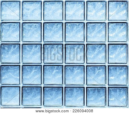 Abstract Background Of Blue Glass Wall Cubes. Thirty Blue Tinted Square Glass Blocks With Natural Li