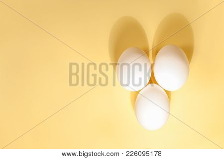 Flat Lay Minimalism. Three White Eggs Are Lying Next To Each Other On The Right Side Of A Yellow Bac