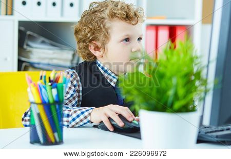 Little Caucasian Schoolboy Looks Like A Boss Working On Computer Sitting At Office Work Place.