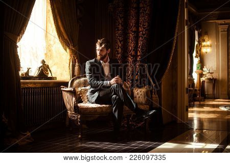 Indoor Shot Of Prosperous Intelligent Serious Businessman Sits On Comfortable Sofa In Rich Room With