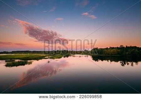 River Landscape In Belarus Or European Part Of Russia In Sunset Time Of Summer Evening. Moon Rising
