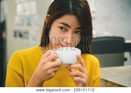 Protrait Of Asian Young Female With Long Black Hair Holding And Tasting Her Coffee In The Coffee Sho