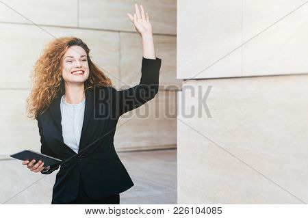 Smiling Happy Businesswoman Dressed Formally, Holding In Hands Modern Tablet Computer, Waving With H