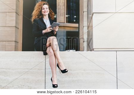 Beautiful Elegant Businesswoman In Formal Clothes And High-heeled Shoes, Having Wavy Hair And Slende