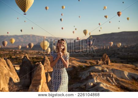 Horizontal Outdoor Shot Of Happy Blonde Young Smiling Woman In Dress Being Excited As Stands On High