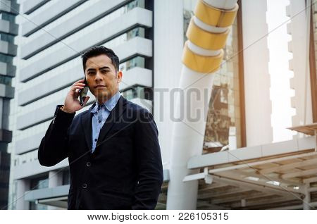 Young Smart Asian Business Man Wearing Modern Black Suit Making Phone Call With Mobile Smart Phone I