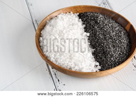 Two Kinds Of Salt. White Sea Salt And Black Himalayan Salt In A Wooden Bowl On White Background