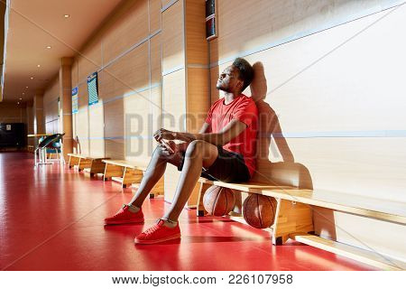 Exhausted Thoughtful Handsome Young African-american Basketball Player Sitting On Bench With Two Bal