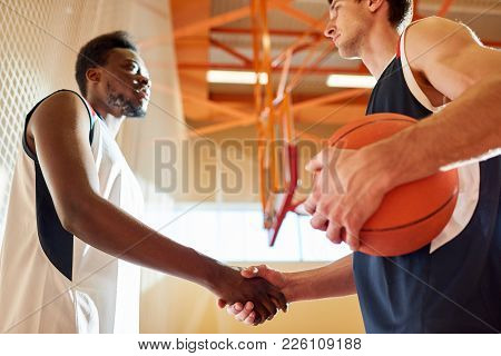 Below View Of Serious Professional Young Interracial Basketball Players Making Handshake Greeting Ea