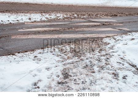 Winter In The City Of Zebra Pedestrian Crossing. Dirty Snow Tracks Auto Car Wheels, Foot Prints Of P