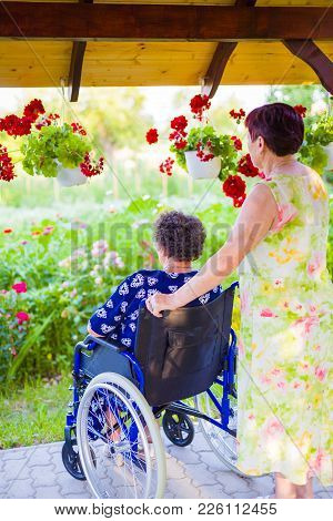 Elder Daughter Taking A Walk With Disabled Mother In Wheelchair.