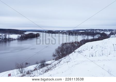 Beautiful River Landscape In Winter. Snowy Hills, And The River Going Into The Distance. Birch Winte