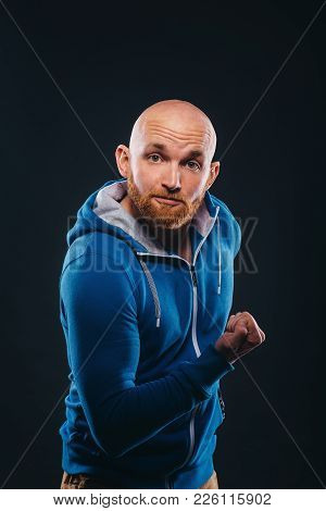 Young Man Jokingly Demonstrates His Biceps On A Black Background