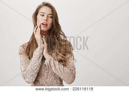 Indoor Shot Of Hot Fair-heired Caucasian Woman Looking Aside While Tenderly Touching Face With Hand,