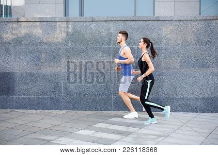 Young Tired, Exhausted Athletic Woman And Man Jogging In City, Running Against The Gray Wall, Copy S