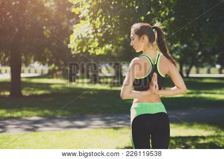 Woman Outdoors Making Asana Exercises. Girl Doing Reverse Prayer Pose, Back And Shoulders Stretching
