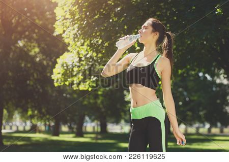 Exhausted Woman Wearing Sportswear Drinking Water From Bottle After Training Outdoors. Stretching, W