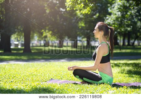 Young Woman Outdoors, Meditation Exercises. Girl Doing Lotus Pose For Relaxation With Closed Eyes An