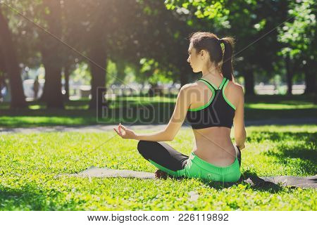 Young Smiling Woman Outdoors, Meditation Exercises. Girl Doing Bufferfly Pose For Relaxation. Wellne