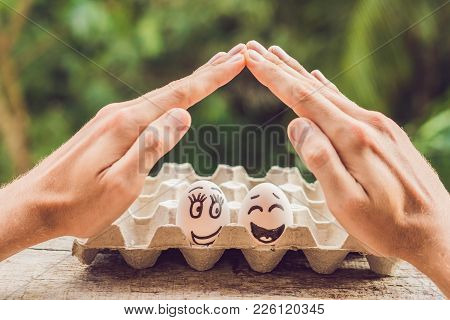 Two Eggs - A Married Couple And Two Man's Open Hands Making A Protection Gesture Family Life Insuran