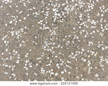 Old Gray Concrete Road Surface And Many Small Stones Of White, Dark And Gray Colors Interspersed Wit