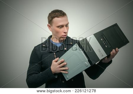 Embarrassed Computer Technician Man Is Looking On Computer In His Hands.