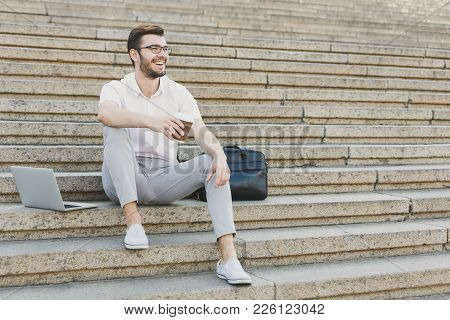 Pensive Businessman Having Rest Outdoors. Young Serene Salesman Sitting On Stairs With Take Away Cof