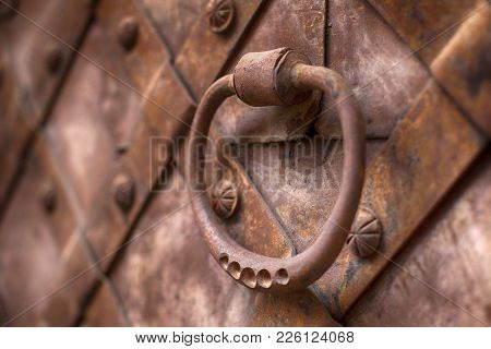 Forged Handle On The Background Of Metal Doors. Fragment Of The Old Iron Door