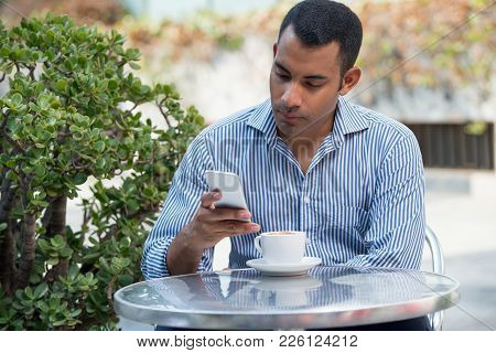 Calm Handsome Man Waiting For Girlfriend On Date While Sitting In Summer Cafe. Serious Successful En