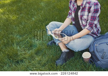 Unrecognizable Woman Sitting Outdoors On Grass With Digital Tablet, Typing, Surfing Internet, Prepar