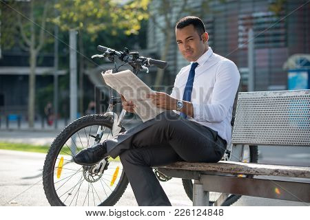 Content Young Manager With Bicycle Resting In Urban Park And Looking At Camera. Cheerful Latin Busin