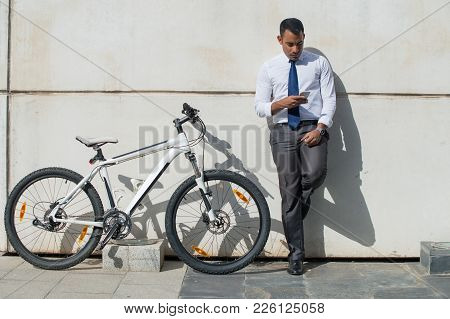 Modern Businessman Checking Email On Phone While Leaning On Wall With Bicycle. Serious Concentrated