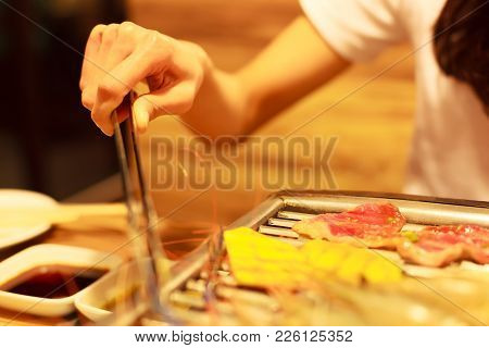 Woman Hand Holding Stainless Steel Hot Food Gripping Tong Clamp Frying Meat And Vegetable Food On Ba