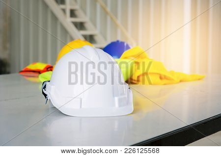 Close Up White Safety Helmet With Reflective Clothing On Desk At Construction Site And Scaffold Back