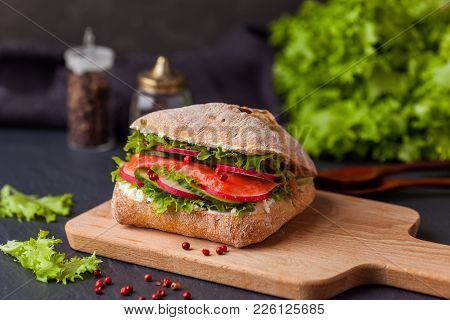 Ciabatta Sandwich With Salmon, Vegetables And Fresh Salad On Wooden Boarde