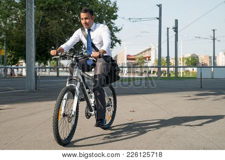 Serious businessman riding bicycle while hurrying to work. Confident young office employee leading healthy lifestyle and travelling on bike. Cycling as daily routine concept poster