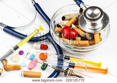 Cigarettes In A Glass Ashtray On A White Background. Treatment Of Lung Cancer.stethoscope And Medica
