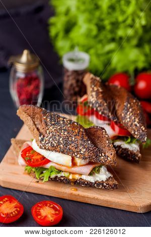 Sandwich With Ham, Poached Egg And Fresh Tomatoes On Wooden Boarde. Dark Background