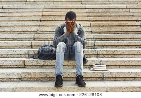 Desperate African-american Student Sitting On Stairs Outdoors In University Campus. Man Closed His F