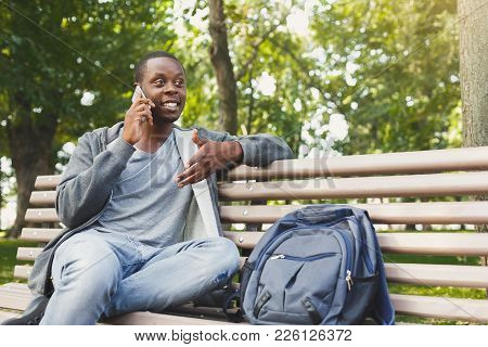 Happy Smiling African-american Student Sitting And Talking On The Phone On The Bench Outdoors In Uni