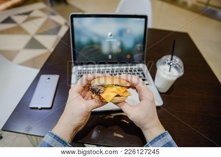 Man Eat Burger In Cafe And Work On Laptop First Person View