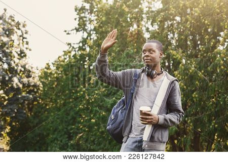 Smiling African-american Student Saying Hello To Someone Outdoors, Having Rest In Campus. Education