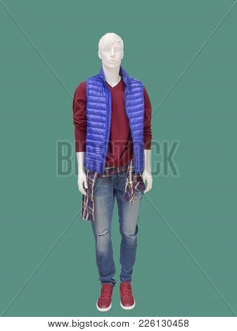Full-length Male Mannequin Dressed In Sleeveless Jacket, Sweater And Blue Jeans, Isolated On Green B