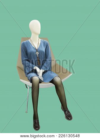 Female Mannequin Sitting On Armchair Over Green Background. No Brand Names Or Copyright Objects.