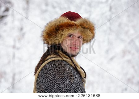 Portrait Of A Viking Warrior Man. Viking Warrior With Chain Mail Leather Spear Walking In Winter Woo