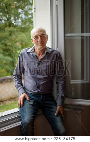 Portait Of Handsome Senior Man Looking At The Camera Standing In Front Of Opened Window In His House