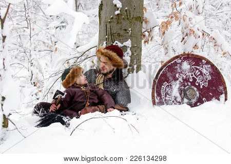 Father And Son Vikings In A Deep Winter Forest And The Father Teaches His Son To Be A Real Viking. V