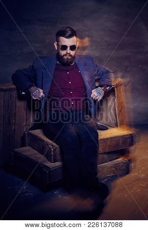 Fashionable Bearded Man In Sunglasses Sitting On Wooden Boxes.