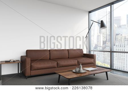 White Living Room Interior With A Brown Sofa, A Poster Hanging Above It, A Panoramic Window And A Co