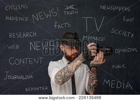 Bearded Dslr Photographer With Tattooes On His Arms Over School Desk Background.